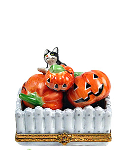 Limoges box cat inside fence with pumpkins