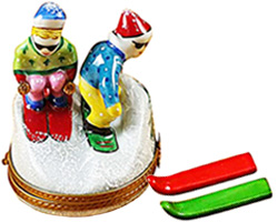 Limoges box skier and snowboarder on hill, with pair of porcelain skis inside